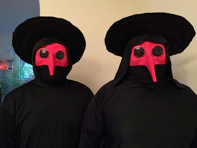 Photograph of two black coated figures, with red, long-nosed masks.