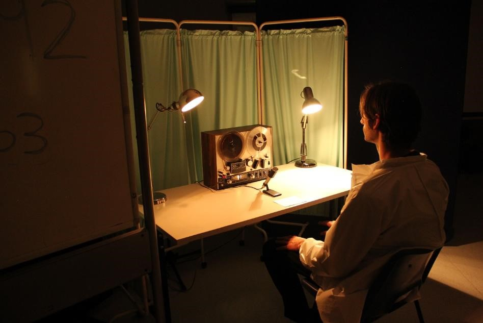 man in a lab coat sitting at a desk with a tape recorder in a dimly lit room